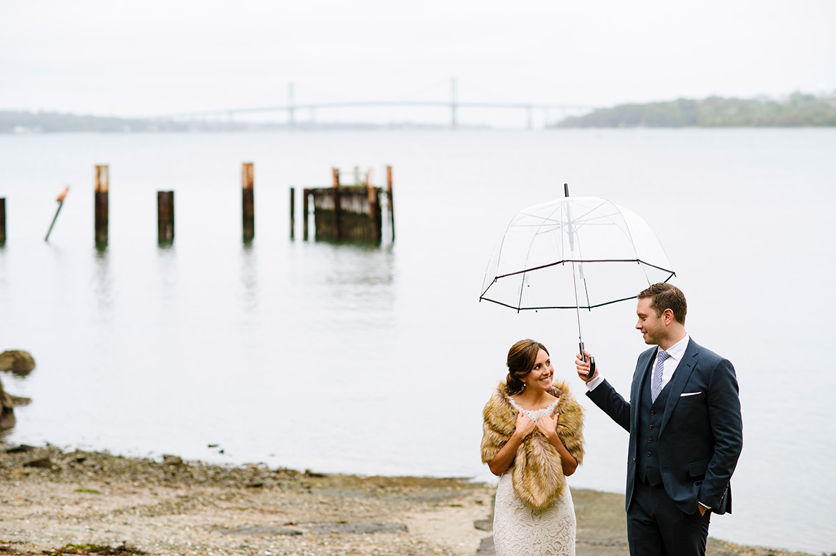 Bride and Groom walk by the water with an umbrella