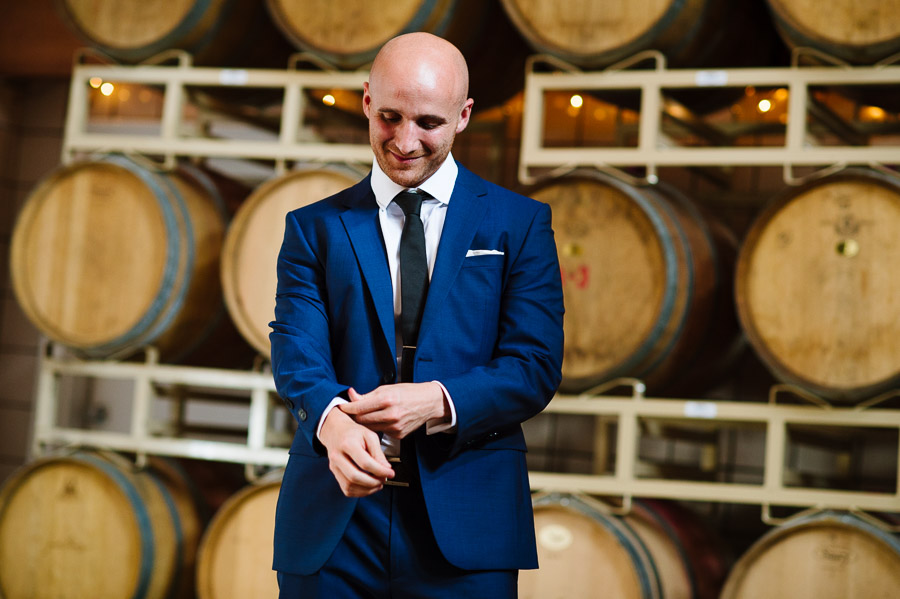 groom getting ready in the barrel room at Jonathan Edwards Winery