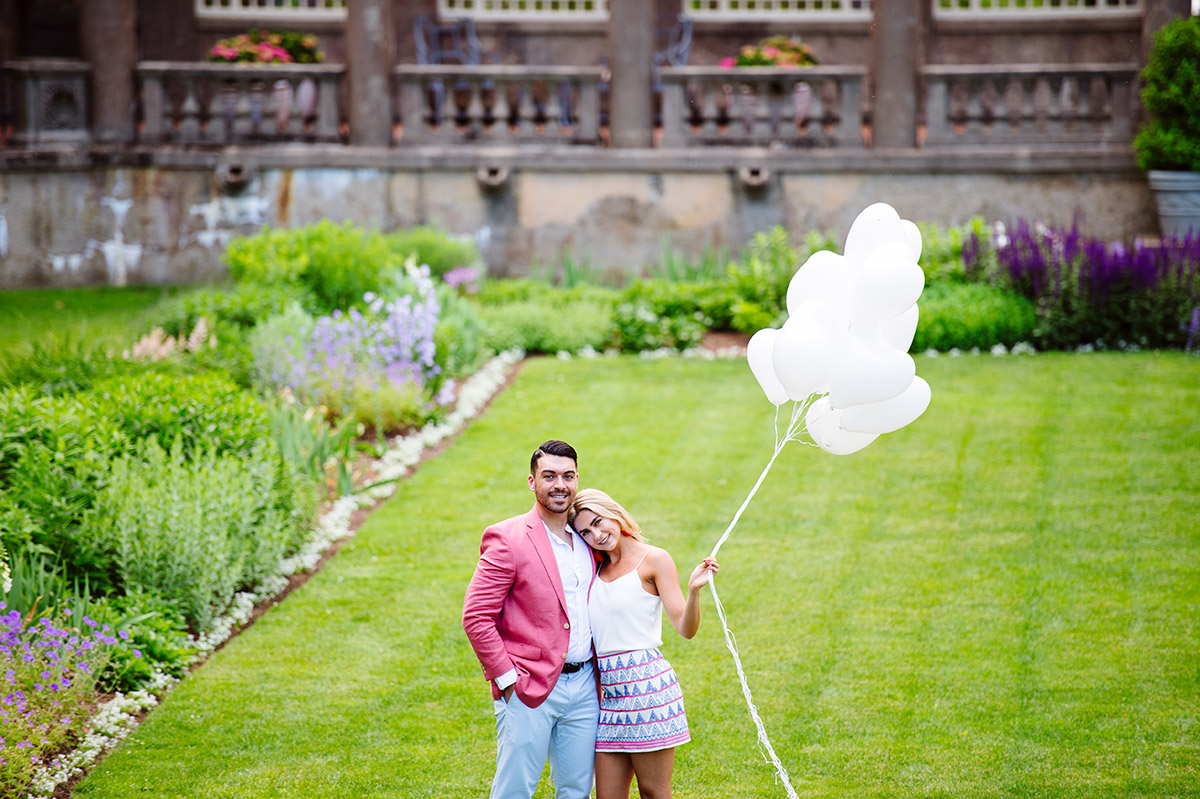 Couple in the Italian Garden at Crane Estate with white heart balloons