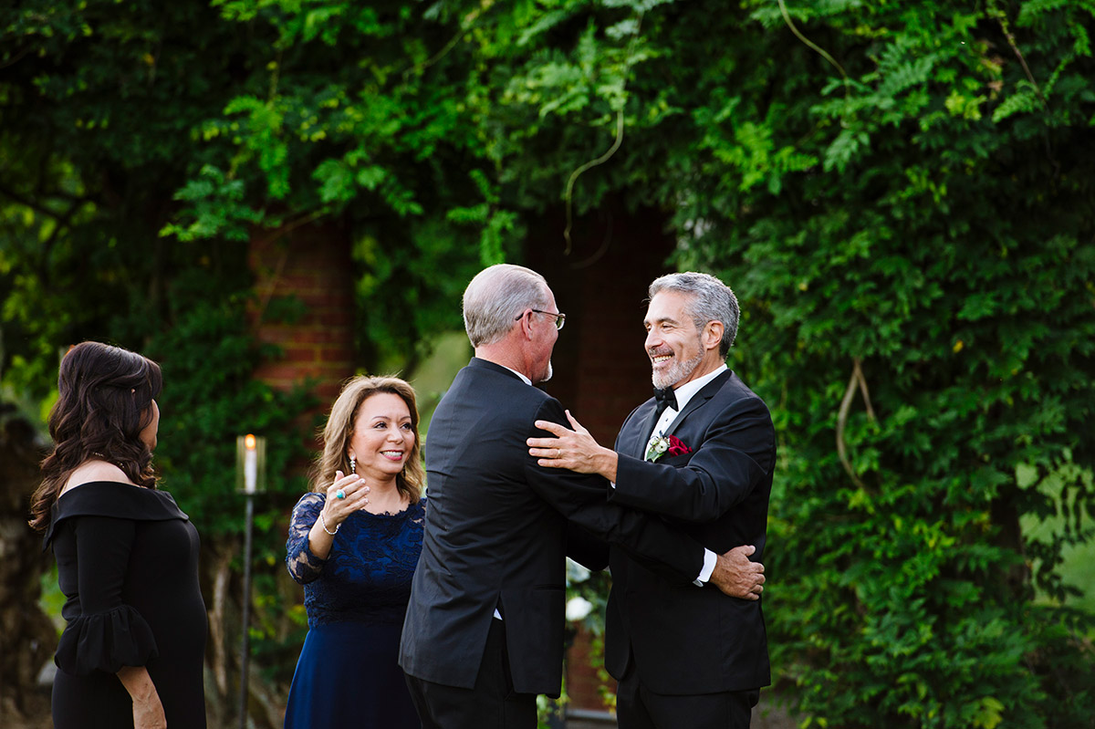 Bride and Groom's parents embrace