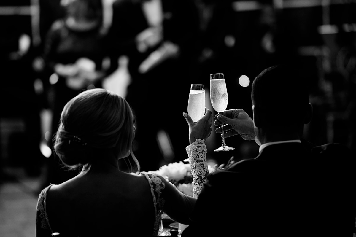 Couple toasts with glowing champagne glasses