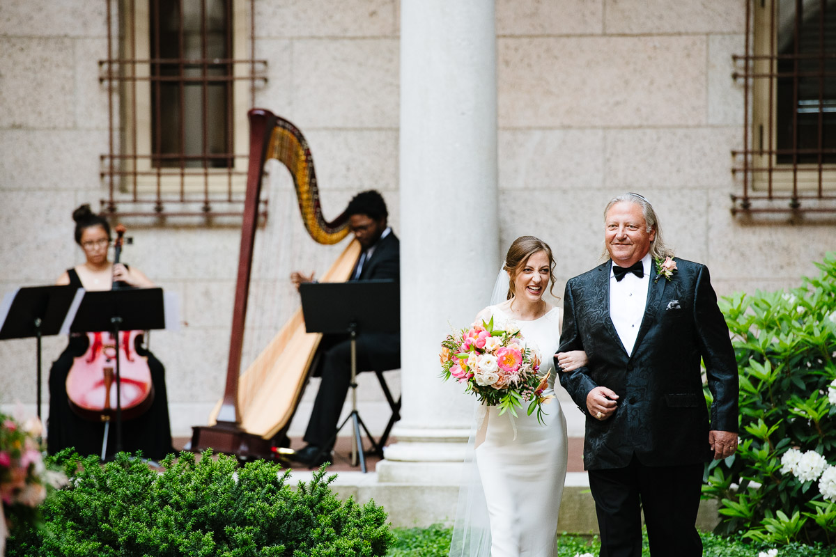Bride processes down the aisle with her father in the courtyard